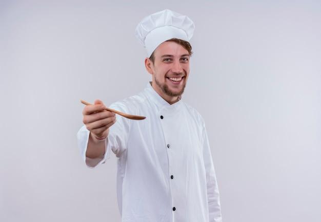 Szczęśliwy młody brodaty szef kuchni w białym mundurze kuchennym i kapeluszu zaprasza do smaku z drewnianą łyżką na dłoni, patrząc na białą ścianę