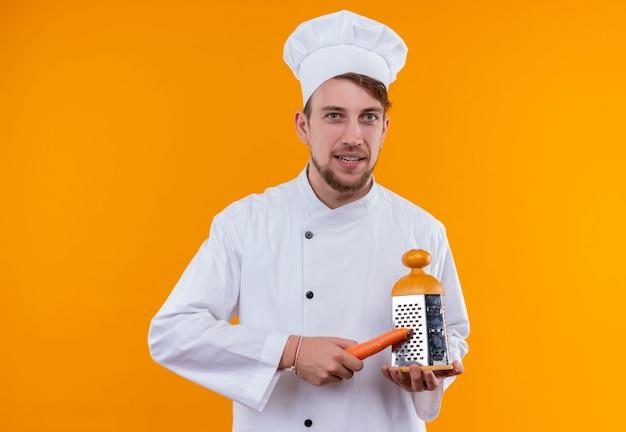 Szczęśliwy młody brodaty szef kuchni w białym mundurze rozdrabnia marchewki z tarką na pomarańczowej ścianie