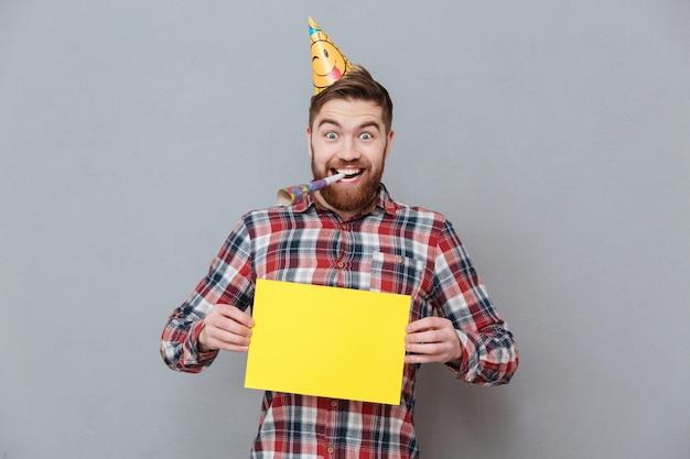 Szczęśliwy młody brodaty urodzinowy mężczyzna trzyma puste miejsce deskę
