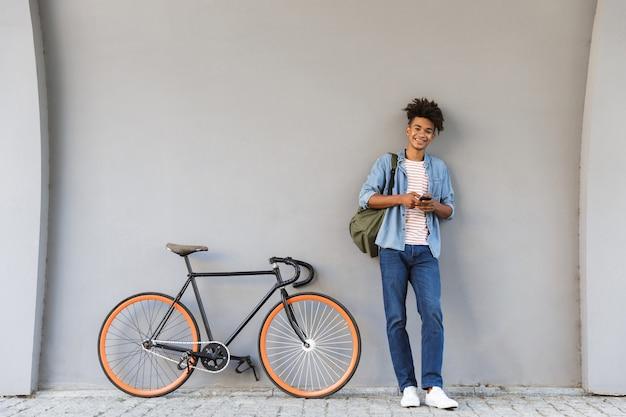 Szczęśliwy młody chłopak chodzenie na zewnątrz z rowerem na czacie przez telefon komórkowy