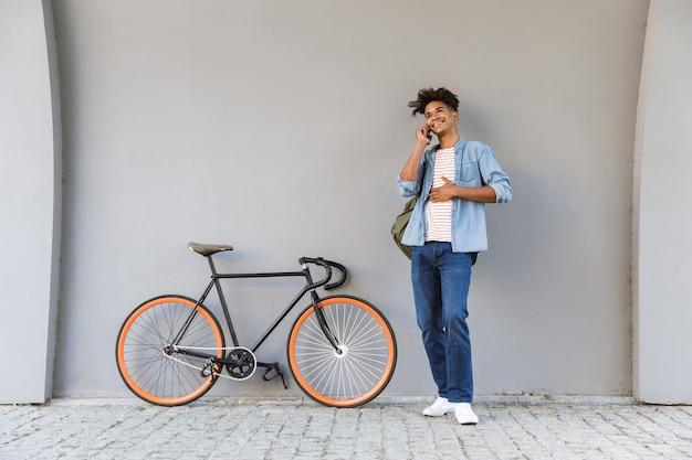 Szczęśliwy młody chłopak chodzenie na zewnątrz z rowerem rozmawia przez telefon komórkowy