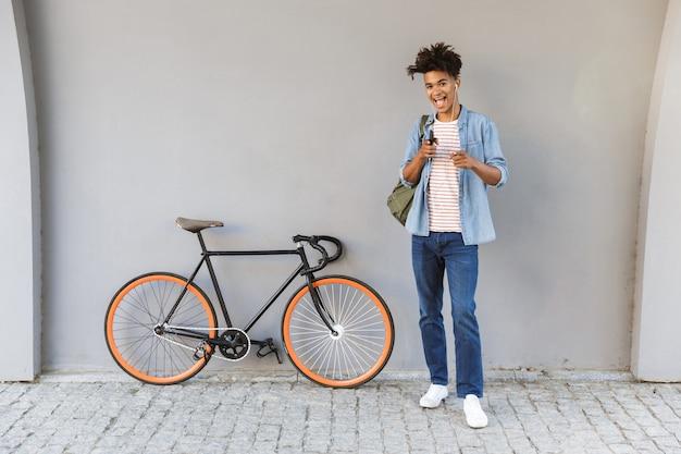 Szczęśliwy młody chłopak chodzenie na zewnątrz z rowerem słuchanie muzyki na czacie przez telefon komórkowy