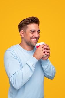 Szczęśliwy młody chłopak ciesząc się gorącym napojem
