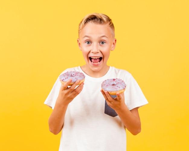 Szczęśliwy młody chłopak gospodarstwa pączki