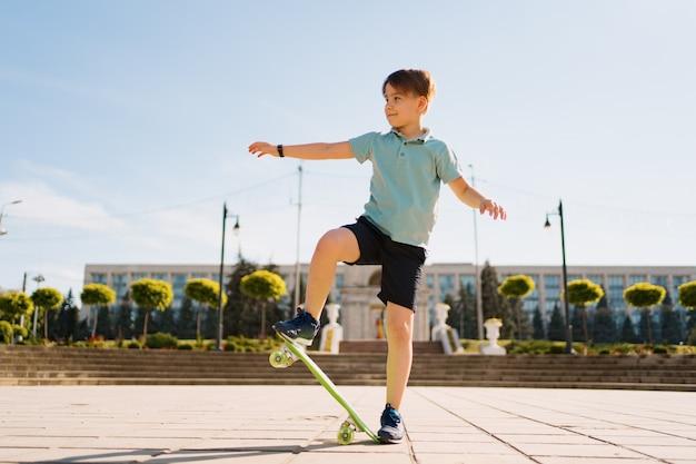 Szczęśliwy młody chłopak gra na deskorolce w parku, kaukaski dziecko jazda konna deska grosza, ćwiczenia deskorolka.
