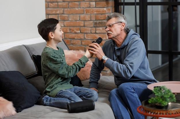 Szczęśliwy młody chłopak i dziadek śpiewają karaoke z kolumną muzyczną w salonie.