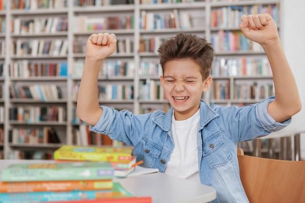 Szczęśliwy młody chłopak krzyczy świętuje egzaminy, zdając lub kończąc pracę domową