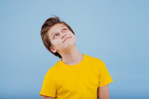 Szczęśliwy młody chłopak patrzy w żółtą koszulkę odizolowaną na niebiesko