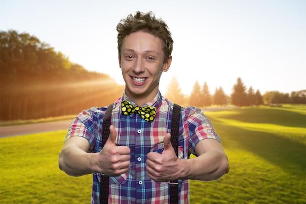 Szczęśliwy młody chłopak pokazuje aprobaty. uśmiechnięty uczeń ubrany w kraciaste koszule z muszką. słoneczna zielona dolina w tle.