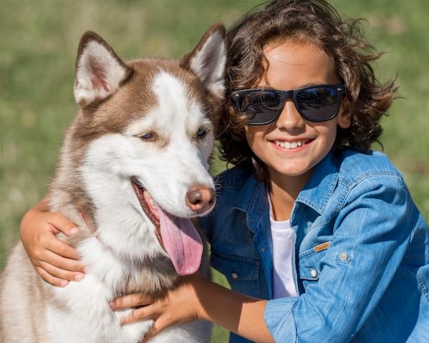Szczęśliwy młody chłopak pozuje z psem w parku