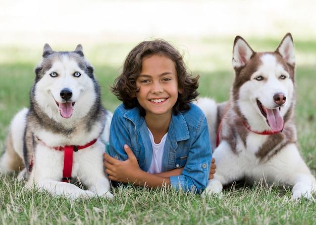 Szczęśliwy młody chłopak pozuje ze swoimi psami w parku
