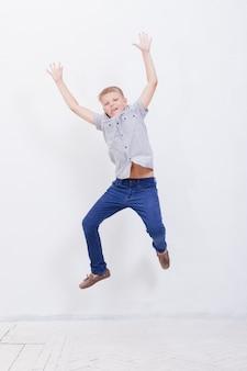 Szczęśliwy młody chłopak skacząc na białym tle