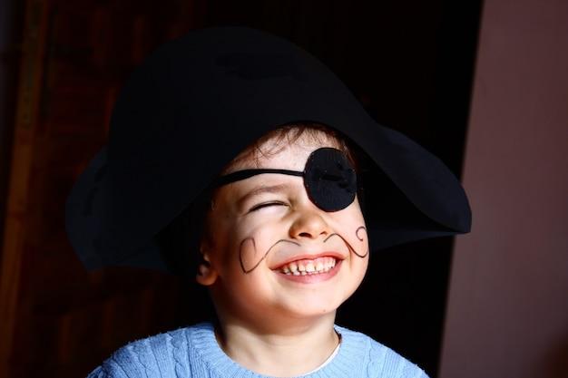 Szczęśliwy młody chłopak ubrany w strój pirata. czarne tło.