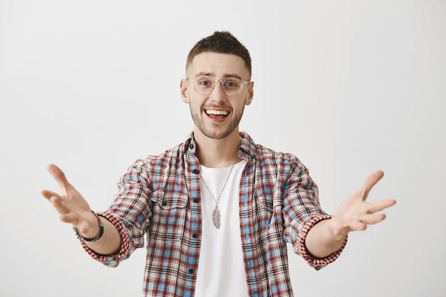 Szczęśliwy młody chłopak w okularach pozowanie