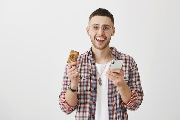 Szczęśliwy młody chłopak w okularach z jego telefonem i kartą
