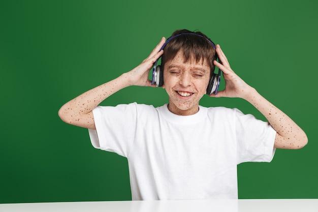 Szczęśliwy młody chłopak z piegami w słuchawkach słucha muzyki i cieszy się siedząc przy stole z zamkniętymi oczami nad zieloną ścianą