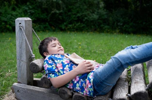 Szczęśliwy młody chłopak z uśmiechniętą twarz leżącą na drewnianej huśtawce w ogrodzie, dziecko relaks w hamaku na zewnątrz z zielonym tłem lasu lato. małe dziecko zabawy grając na zewnątrz w lesie.