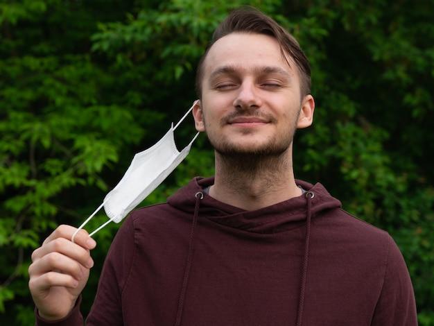 Szczęśliwy młody chłopak zdejmuje maskę medyczną i oddycha świeżym powietrzem w przyrodzie