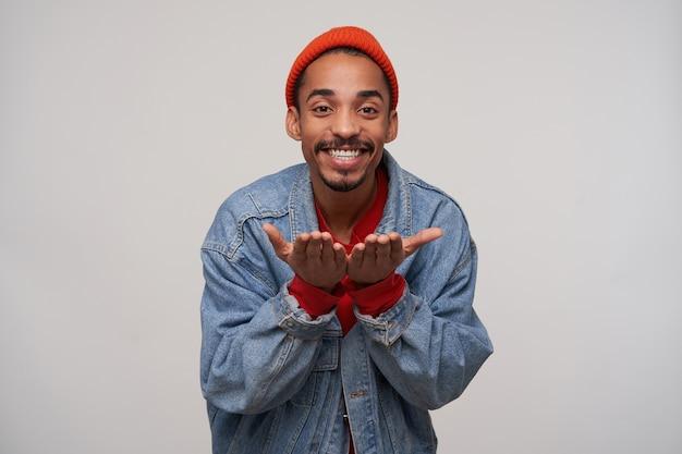 Szczęśliwy młody ciemnoskóry, brodaty brunetka mężczyzna wygląda pozytywnie z uroczym uśmiechem i trzymając ręce podniesione, pozując na białej ścianie w zwykłych ubraniach