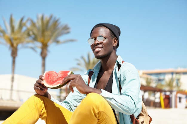Szczęśliwy młody ciemnoskóry mężczyzna podróżnik w stylowych ubraniach siedzi na plaży i je arbuza, ma zrelaksowany wygląd, ciesząc się słoneczną pogodą podczas letnich wakacji w tropikalnym kraju