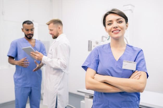 Szczęśliwy młody cross-armed lekarz w mundurze stojąc przed kamerą z kolegami konsultującymi na tle