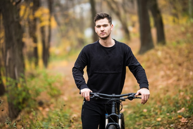 Szczęśliwy młody cyklisty mężczyzna jedzie na jego bicyklu na szkoleniu w jesień lesie