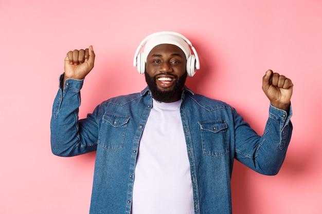 Szczęśliwy młody człowiek afro-amerykański tańczy i słucha muzyki w słuchawkach, pompuje pięści i uśmiecha się, stojąc na różowym tle