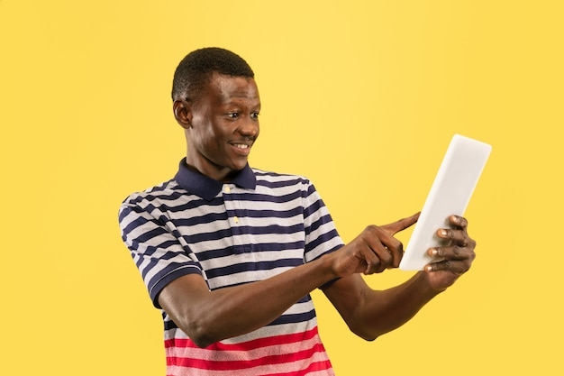 Szczęśliwy młody człowiek afro-amerykański z tabletem na białym tle na żółtym studio