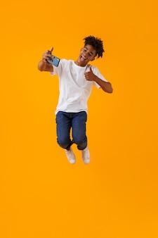 Szczęśliwy młody człowiek afrykański skaczący na białym tle nad żółtą przestrzenią wziąć selfie przez telefon pokazując kciuk do góry.