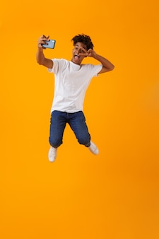 Szczęśliwy młody człowiek afryki skoki na białym tle nad żółtą przestrzenią wziąć selfie przez telefon.