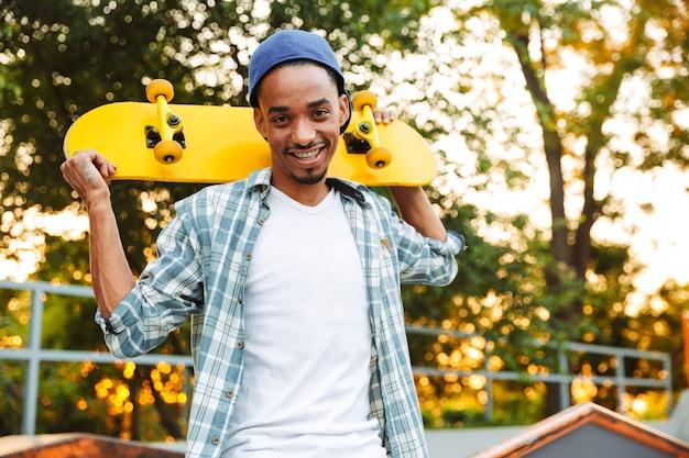 Szczęśliwy młody człowiek afryki z deskorolką