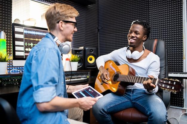 Szczęśliwy młody człowiek afryki z gitarą i jego kolega siedzi w nowoczesnym studio nagrań dźwiękowych i pracuje nad nową ścieżką dźwiękową