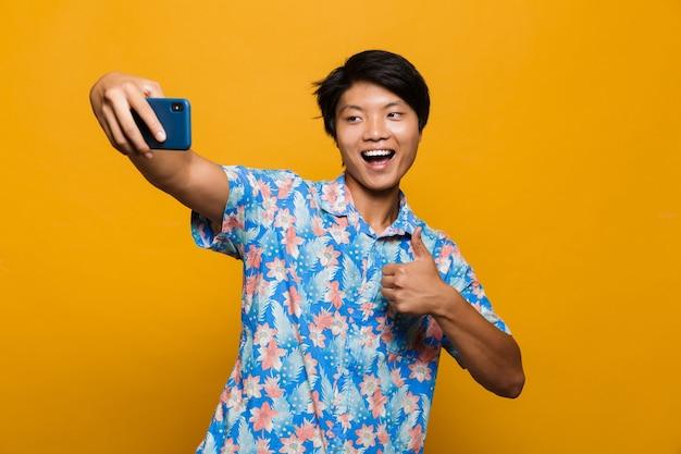 Szczęśliwy młody człowiek azjatycki stojący na białym tle nad żółtą przestrzenią wziąć selfie przez telefon komórkowy z kciuki do góry.