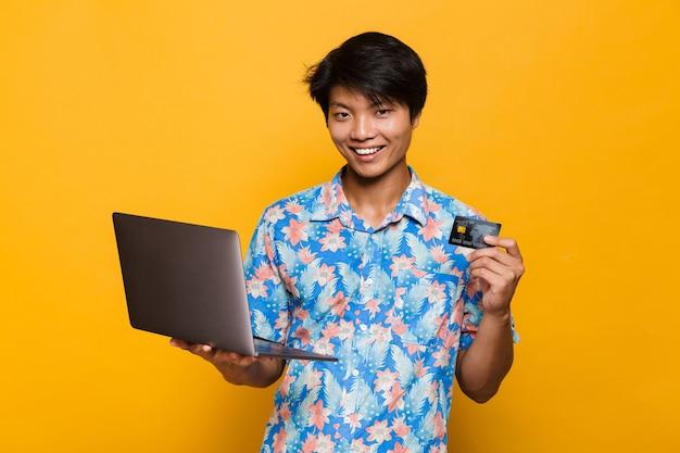 Szczęśliwy młody człowiek azjatyckich stojący na białym tle nad żółtą przestrzenią przy użyciu komputera przenośnego posiadającego kartę debetową.