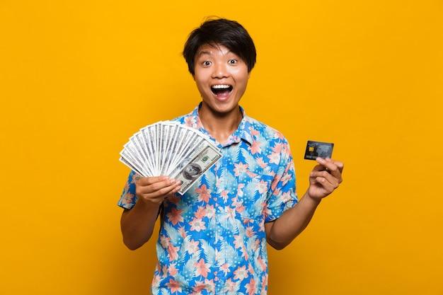 Szczęśliwy młody człowiek azjatyckich stojący na białym tle nad żółtą przestrzenią, trzymając pieniądze i kartę kredytową.
