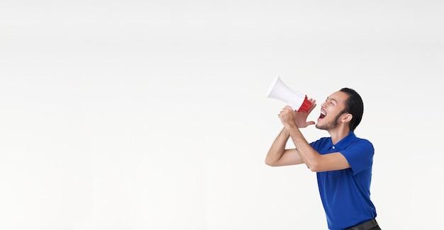 Szczęśliwy młody człowiek azji w niebieskiej koszuli krzycząc ogłaszają w megafon na białym tle na białym tle w studio.