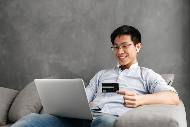 Szczęśliwy młody człowiek azji za pomocą laptopa