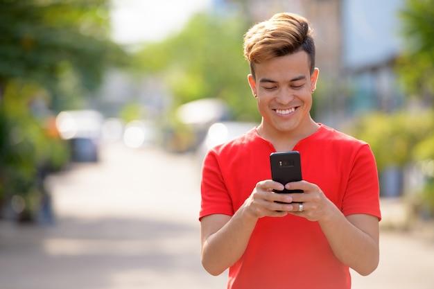 Szczęśliwy młody człowiek azji za pomocą telefonu na ulicach na zewnątrz