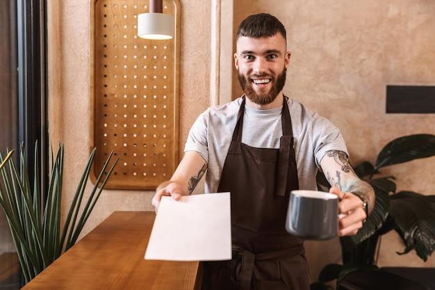 Szczęśliwy młody człowiek barista ubrany w fartuch stojący w kawiarni, pokazujący filiżankę kawy i pusty notatnik