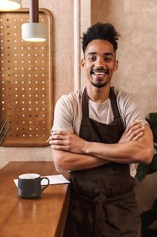 Szczęśliwy młody człowiek barista ubrany w fartuch stojący w kawiarni, z założonymi rękoma