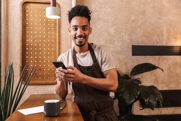 Szczęśliwy młody człowiek barista w fartuchu stojący w kawiarni, przy użyciu telefonu komórkowego