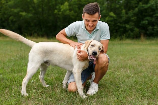 Szczęśliwy młody człowiek bawi się ze swoim przyjacielem
