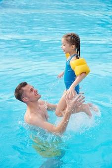Szczęśliwy młody człowiek bawi się ze swoją uroczą córeczką w basenie przed kamerą, spędzając razem weekend w centrum spa