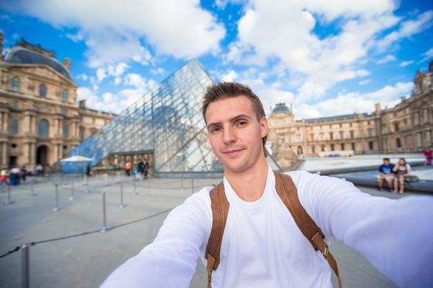 Szczęśliwy młody człowiek bierze selfie fotografię w paryż, francja