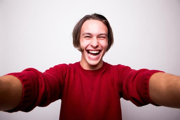 Szczęśliwy młody człowiek biorąc autoportret za pomocą inteligentnego telefonu na białym tle nad białą ścianą