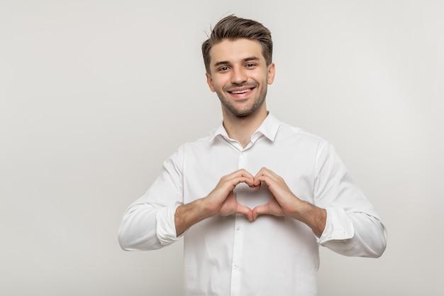 Szczęśliwy młody człowiek biznesu pokazując kształt serca z rękami na białym tle