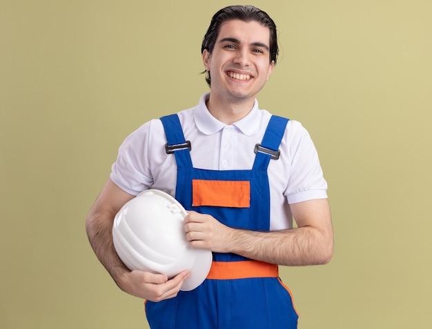 Szczęśliwy młody człowiek budowniczy w mundurze budowy, trzymając kask, patrząc z przodu z uśmiechem na twarzy stojącej nad zieloną ścianą
