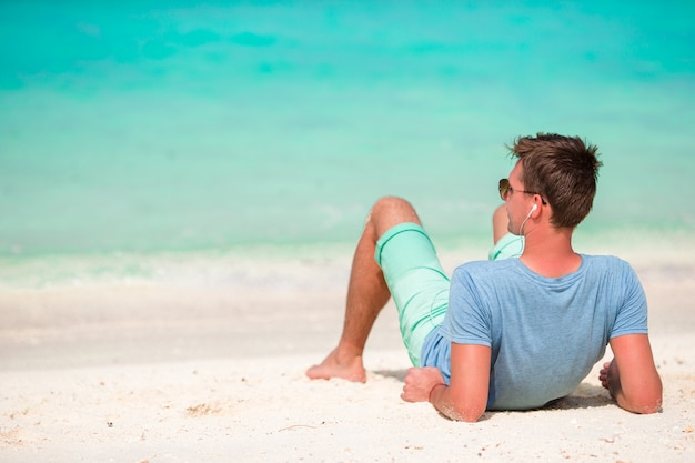 Szczęśliwy młody człowiek cieszy się czas na białej piaskowatej plaży
