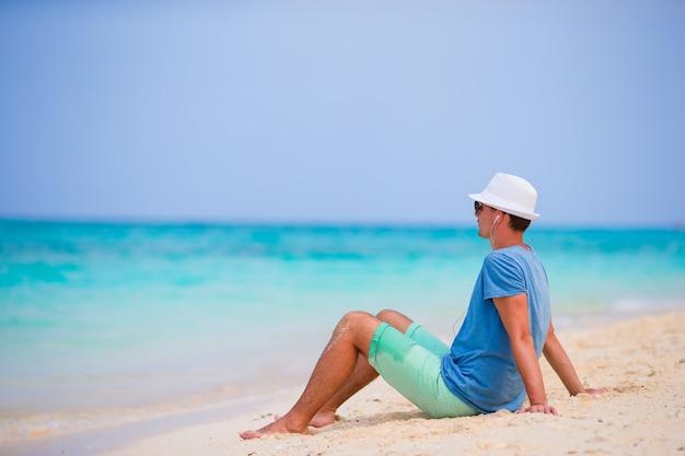 Szczęśliwy młody człowiek cieszy się muzykę na białej piaskowatej plaży