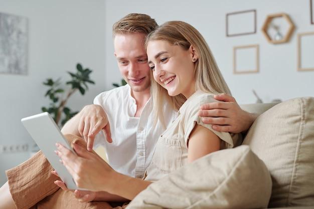 Szczęśliwy młody człowiek czuły, obejmując swoją całkiem uśmiechniętą żonę i wskazując na ekran cyfrowego tabletu podczas przewijania sklepu internetowego